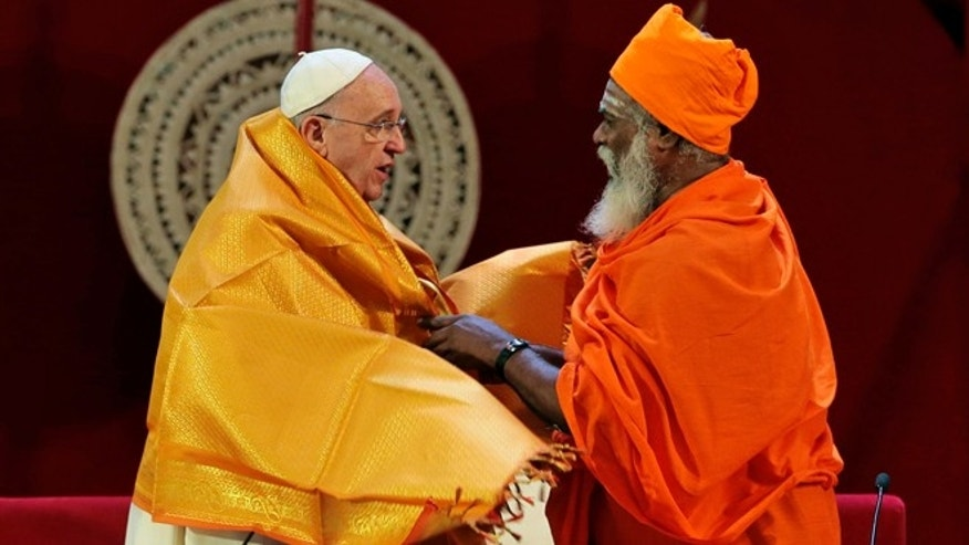 Jan. 13, 2015: Sri Lankan Hindu priest Kurakkal Somasundaram, right, presents a shawl to Pope Francis during an inter-religious meeting in Colombo, Sri Lanka.