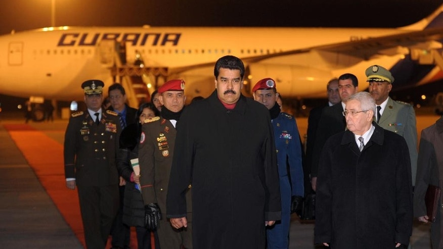 Venezuela's President Nicolas Maduro, front left, walks with Algeria's Speaker of the Senate Abdelkader Bensalah during a welcome ceremony for Maduro at the airport in Algiers, Algeria, Monday, Jan. 12, 2015. Maduro is touring several OPEC nations to drum up support for a production cut to boost prices. (AP Photo/Sidali Djarboud)