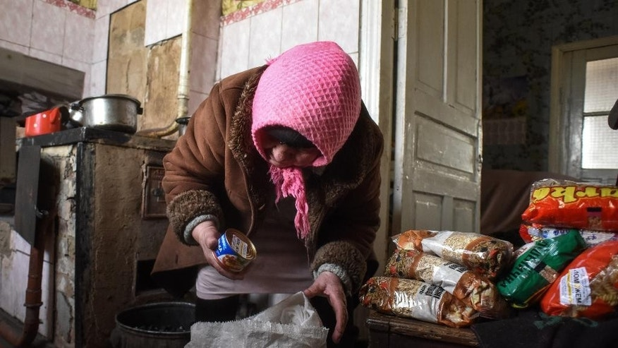 In this Monday, Jan. 12, 2015 photo, Maria Ivanovna, no family name given, unpacks humanitarian aid she received from the charitable foundation of Ukrainian billionaire Rinat Akhmetov, whose vast wealth is founded on the industrial output of Donetsk coal-rich region, at her house at the outskirts of Donetsk, Eastern Ukraine. Akhmetov is contentious figure in eastern Ukraine. Although a major provider of employment, he is regarded with profound suspicion by much of the impoverished local population. Still, his standing improves with every consignment of goods that reaches separatist-held regions. Amnesty International said it received reports before the New Year holidays of volunteer battalions fighting alongside Ukrainian government forces of preventing the Akhmetov convoys from getting through. The battalion justified their actions by arguing that the food and clothes in the trucks could ultimately help to support the separatist cause, Amnesty says. (AP Photo/ Mstyslav Chernov)