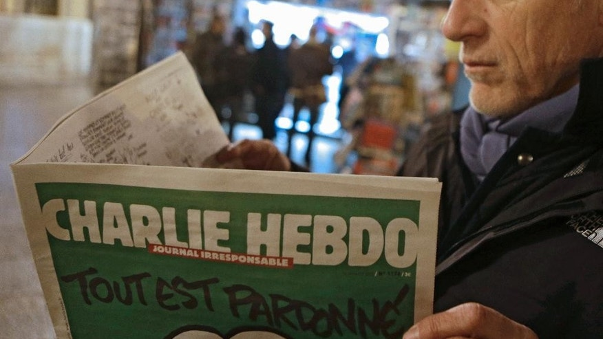 "Jean Paul Bierlein reads the latest issue of Charlie Hebdo outside a newsstand in Nice, southeastern France, Wednesday, Jan. 14, 2015. In an emotional act of defiance, Charlie Hebdo resurrected its irreverent and often provocative newspaper, featuring a caricature of the Prophet Muhammad on the cover that drew immediate criticism and threats of more violence. The black letters on the front page read: ""All is forgiven."" (AP Photo/Lionel Cironneau)"