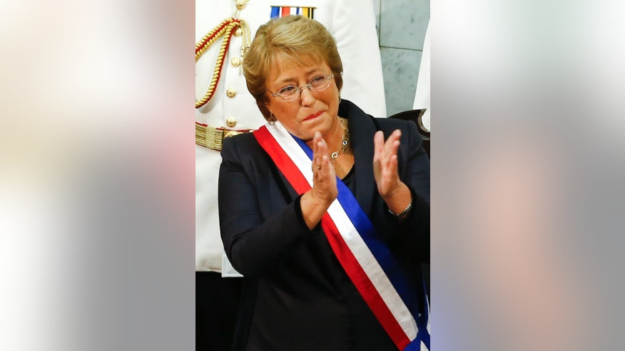 "FILE - In this March 11, 2014 file photo, Chile's new President Michelle Bachelet, wearing the presidential sash, applauds after being sworn-in as president in the Chilean Congress in Valparaiso, Chile. The Senate voted Wednesday, Jan. 14, 2015, to end a dictatorship-era electoral system that has squeezed out independent candidates and guaranteed an outsized presence in Congress for the center-right and center-left blocs. Bachelet had promised to finally end it calling the system a ""thorn pounded into the center"" of Chilean democracy. (AP Photo/Victor R. Caivano, File)"