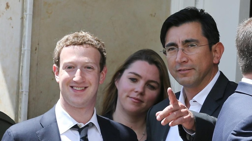 Facebook founder and CEO Mark Zuckerberg, left, and Minister of Information Technologies and Communications Diego Molano, pose for photographers outside the presidential palace in Bogota, Colombia, Wednesday, Jan. 14, 2015. Zuckerberg is in Bogota to to launch an app providing free basic Internet service via cellphone connections in the South American country. (AP Photo/Fernando Vergara)
