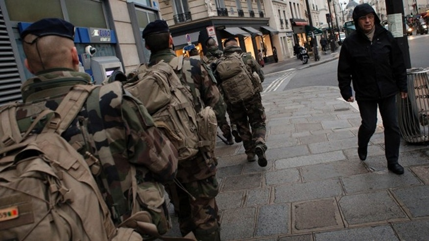 Jan. 14, 2015: Soldiers patrol the street in Paris. French police say as many as six members of a terrorist cell that carried out the Paris attacks may still be at large, including a man seen driving a car registered to the widow of one of the gunmen. The country has deployed 10,000 troops to protect sensitive sites, including Jewish schools and synagogues, mosques and travel hubs.