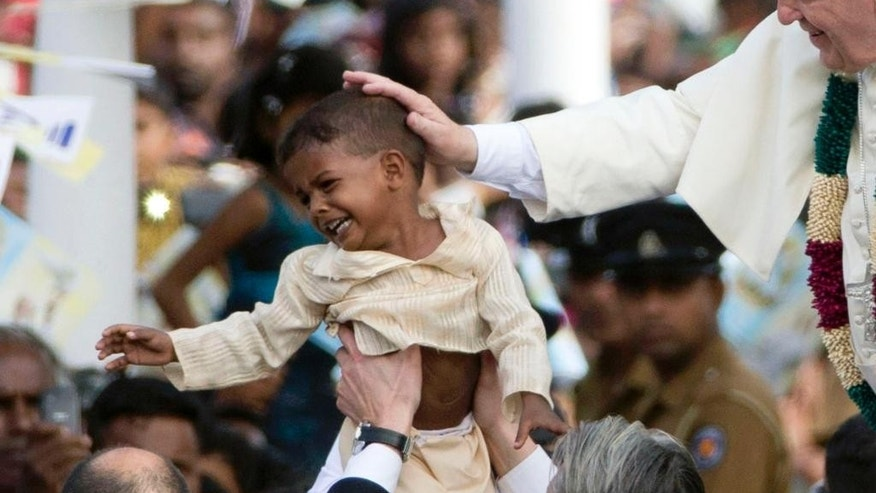 FILE - In this Wednesday, Jan. 14, 2015, file photo, Pope Francis blesses a child as he arrives in Madhu, Sri Lanka. Pope Francis has worked to avoid cloaking himself in the mystical power that popes are so often endowed with by believers, but still many of the thousands who came out to see him hoped for a touch or a blessing from him. (AP Photo/Alessandra Tarantino, Pool, File)