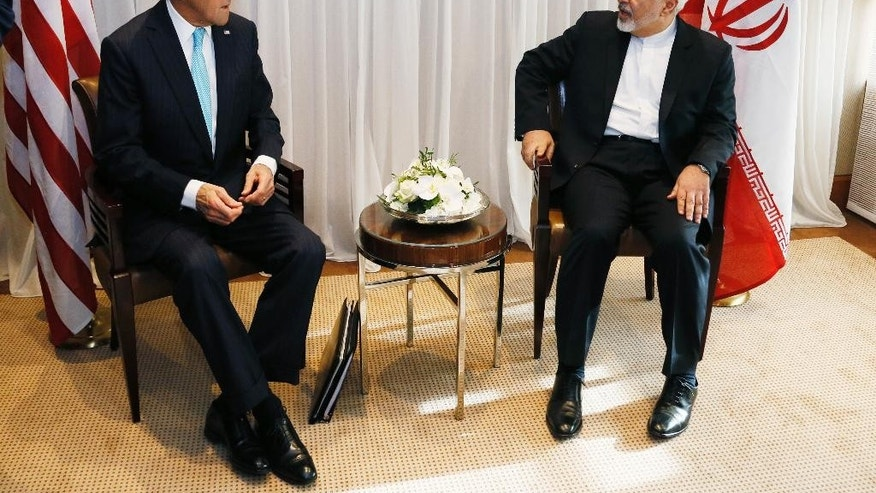 U.S. Secretary of State John Kerry, left, waits with Iranian Foreign Minister Mohammad Javad Zarif before a meeting in Geneva, Switzerland Wednesday, Jan. 14, 2015. Zarif said on Wednesday that his meeting with Kerry was important to see if progress could be made in narrowing differences on his country's disputed nuclear program.  (AP Photo/Rick Wilking, Pool)