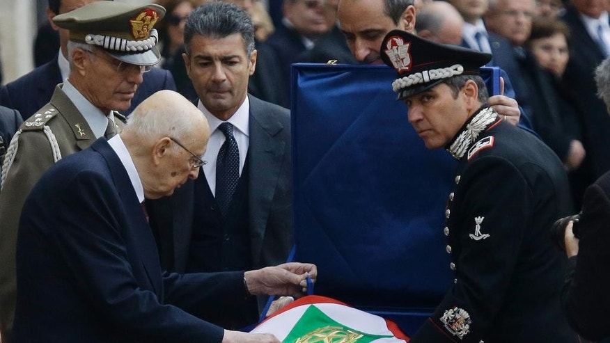 Italy's President Giorgio Napolitano, left, touches the Presidential flag as he leaves the Quirinal presidential palace in Rome, Wednesday, Jan. 14, 2015.  Italy's President Giorgio Napolitano has resigned as promised, less than two years after accepting an unprecedented second term as head of state because squabbling lawmakers couldn't agree on a successor. The Quirinal presidential palace said Napolitano, who turns 90 this year, signed his formal resignation late Wednesday morning. (AP Photo/Gregorio Borgia)