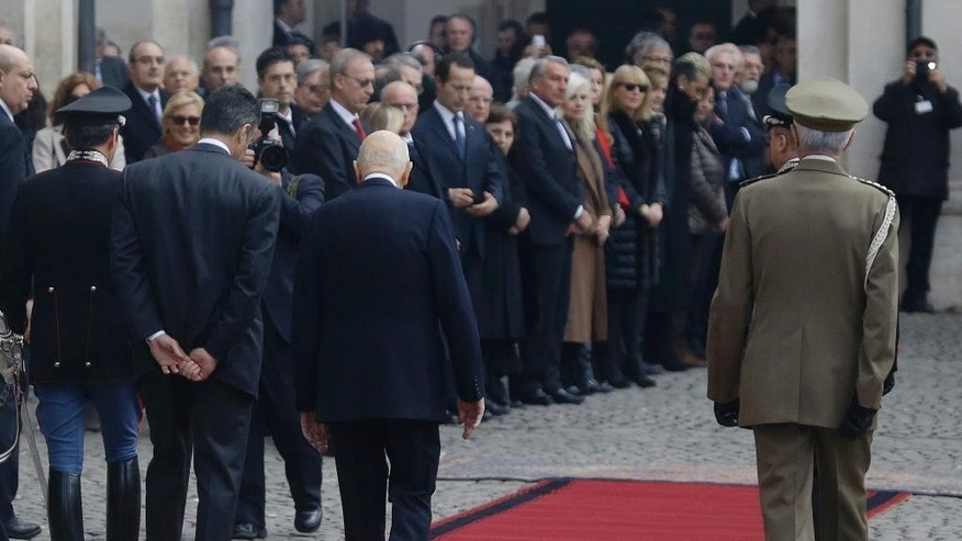 Italy's President Giorgio Napolitano, center, back to the camera, leaves the Quirinal presidential palace in Rome, Wednesday, Jan. 14, 2015.  Italy's President Giorgio Napolitano has resigned as promised, less than two years after accepting an unprecedented second term as head of state because squabbling lawmakers couldn't agree on a successor. The Quirinal presidential palace said Napolitano, who turns 90 this year, signed his formal resignation late Wednesday morning. (AP Photo/Gregorio Borgia)