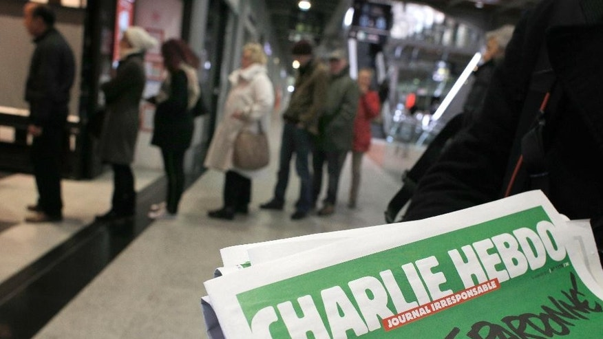 People queue up to buy the new issue of Charlie Hebdo newspaper at a newsstand in Paris Wednesday, Jan. 14, 2015. Charlie Hebdo's defiant new issue sold out before dawn around Paris on Wednesday, with scuffles at kiosks over dwindling copies of the paper fronting the Prophet Muhammad. In the city still shaken by the deaths of 17 people at the hands of Islamic extremists, a controversial comic who appeared to be praising the men was taken into custody. (AP Photo/Christophe Ena)