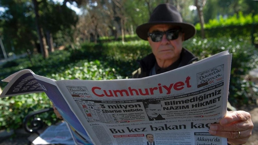 A man reads Cumhuriyet, the leading pro-secular Turkish newspaper, in Istanbul, Turkey, Wednesday, Jan. 14, 2015. Cumhuriyet said police stopped trucks as they left its printing center to check the paper's content after it decided to print a selection of Charlie Hebdo caricatures. Cumhuriyet said police allowed distribution of the newspaper to proceed on Wednesday after verifying that the satirical French newspaper's controversial cover featuring the Prophet Muhammad was not published.(AP Photo)