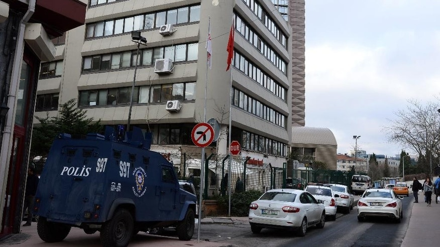 A police car stationed outside the headquarters of Cumhuriyet, the leading pro-secular Turkish newspaper, in Istanbul, Turkey, Wednesday, Jan. 14, 2015. Cumhuriyet said police stopped trucks as they left its printing center to check the paper's content after it decided to print a selection of Charlie Hebdo caricatures. Cumhuriyet said police allowed distribution of the newspaper to proceed on Wednesday after verifying that the satirical French newspaper's controversial cover featuring the Prophet Muhammad was not published. (AP Photo)