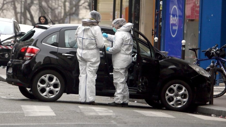 FILE - In this Wednesday, Jan. 7, 2015, file photo, forensic experts examine the car believed to have been used as the escape vehicle by gunmen who attacked the French satirical newspaper Charlie Hebdo's office, in Paris.  One week since the unleashing of the lethal Paris terror attacks, investigators on Wednesday Jan. 14, 2015, are still unraveling the complex, overlapping contacts among the perpetrators and their suspected accomplices in an intricate piece of detective work ranging from the Paris suburbs to the Balkans and Turkish-Syrian border. (AP Photo / FILE)