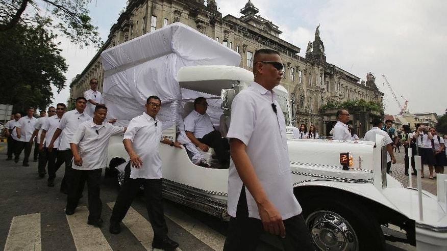 In this Wednesday, Jan. 14, 2015 photo, members of the Philippine Presidential Security Group walk beside a vehicle during a practice run as they prepare for the visit of Pope Francis in Manila, Philippines.  The Philippine government will deploy up to 50,000 police and troops - nearly a fourth of its forces - to ward off any threat, keep ecstatic crowds from mobbing the pontiff and prevent stampedes and crimes.  (AP Photo/Aaron Favila)