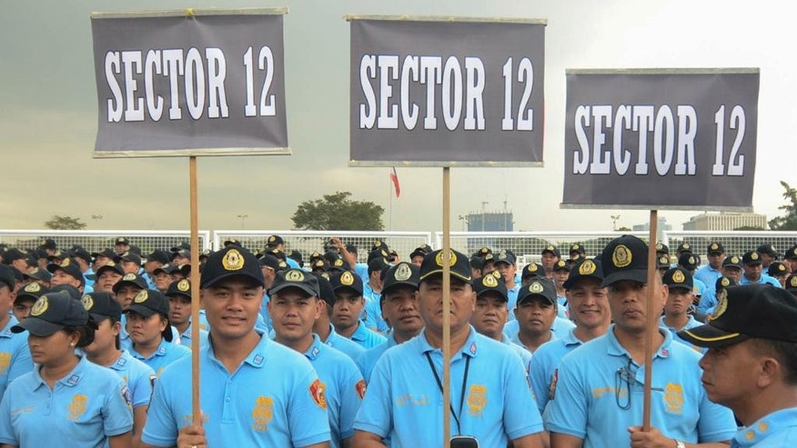 In this Wednesday, Jan. 14, 2015 photo, police officers prepare to be deployed to their respective areas to provide security for visiting Pope Francis at the Rizal Park in Manila, Philippines. The Philippine government will deploy up to 50,000 police and troops - nearly a fourth of its forces - to ward off any threat, keep ecstatic crowds from mobbing the pontiff and prevent stampedes and crimes.  (AP Photo/Alecs Ongcal)