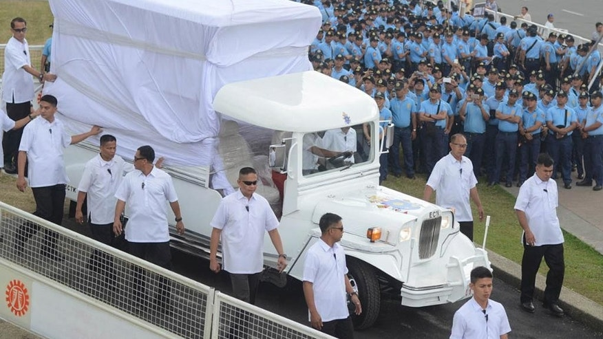 In this Wednesday, Jan. 14, 2015 photo, hundreds of police officers watch members of the Philippine Presidential Security Group walk beside a vehicle during a practice run as they prepare for the visit of Pope Francis in Manila, Philippines. The Philippine government will deploy up to 50,000 police and troops - nearly a fourth of its forces - to ward off any threat, keep ecstatic crowds from mobbing the pontiff and prevent stampedes and crimes. (AP Photo/Alecs Ongcal)