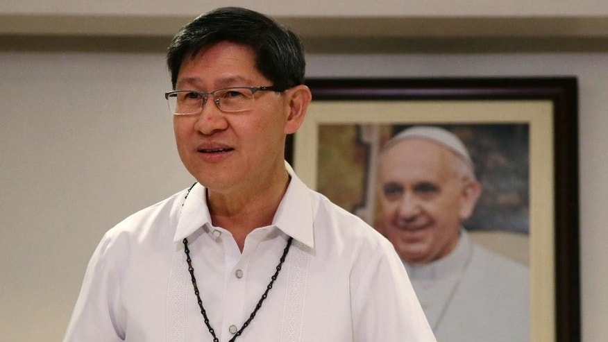 FILE - In this July 29, 2014 file photo, Manila Archbishop Cardinal Luis Antonio Tagle prepares for a simultaneous announcement with the Vatican on the five-day Apostolic visit of Pope Francis to the Philippines in mid-January in 2015, in Manila, Philippines. Pope Francis will be welcomed in the Catholic heartland on Thursday, Jan. 15, 2015, by the Filipino cardinal who might one day succeed him: a boyish-looking priest who rode the bus as a bishop and has impressed many with a humble life, intellect and compassion for the poor. (AP Photo/Bullit Marquez, File)