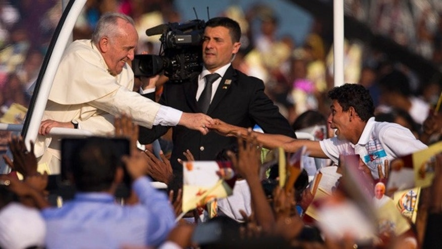 Jan. 14, 2015: A devotee stretches out his hand to touch the hand of Pope Francis as he arrives to hold a mass at Colombo's seafront Galle Face Green for the canonization ceremony of Joseph Vaz. (AP Photo/Saurabh Das)