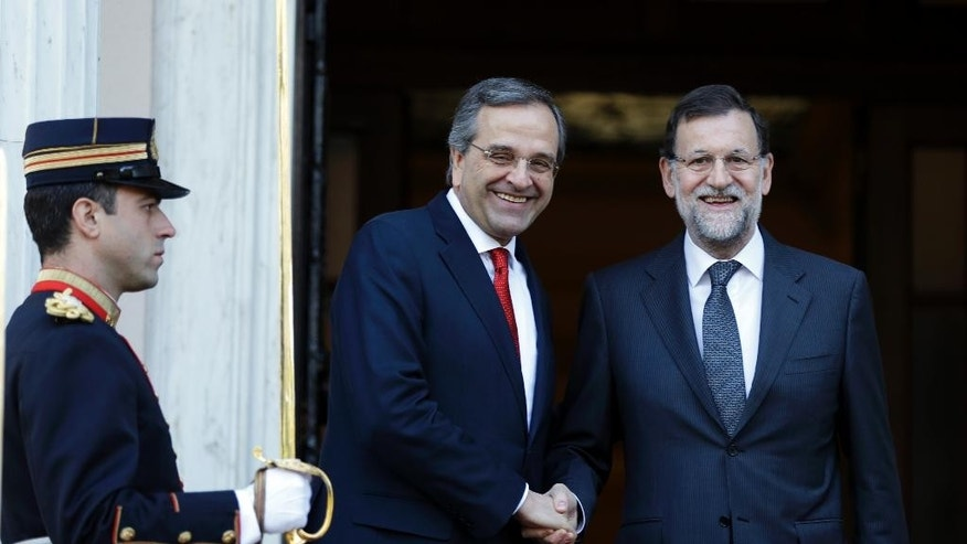 Greece's Prime Minister Antonis Samaras, centre left, welcomes his Spanish counterpart Mariano Rajoy at the Maximos Mansion in Athens on Wednesday, Jan. 14, 2015. Rajoy is in Greece to express support for the country's draconian bailout program, ahead of a general election that could see his fellow conservatives lose power to leftwing challengers. (AP Photo/Thanassis Stavrakis)