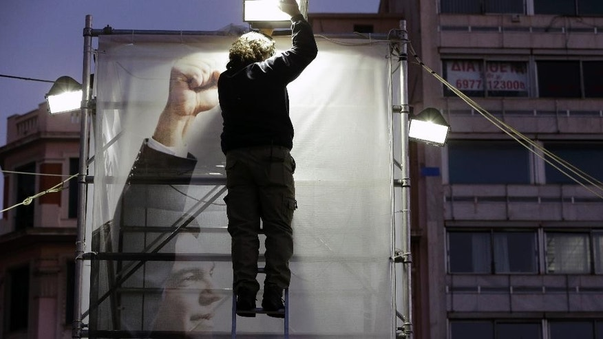 An electrician adjusts a spotlight over a photograph of the opposition leader Alexis Tsipras at the election kiosk of the anti-bailout Syriza party, in central Athens, on Wednesday, Jan. 14, 2015.  Samaras' New Democracy party is facing elections on Jan. 25 and trailing in opinion polls to the leftwing Syriza party, which is demanding that at least half of the Greece's 240 billion euro ($283 billion) bailout loans be forgiven. (AP Photo/Thanassis Stavrakis)