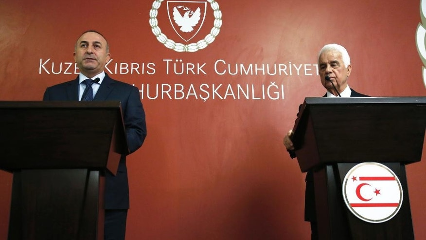 """Turkish Foreign Minister Mevlut Cavusoglu, and Turkish Cypriot leader Dervis Eroglou speak to the media during a press conference after their meeting in the Turkish Cypriot breakaway north part of the divided capital Nicosia, Wednesday, Jan 14 , 2015. United Nations envoy for Cyprus, Norway's Espen Barth Eide says deadlocked talks to reunify ethnically split Cyprus are """"moving in the wrong direction"""" amid a dispute over rights to search for offshore gas. Cavusoglu is in Cyprus for one-day visit for talks. (AP Photo/Petros Karadjias)"""