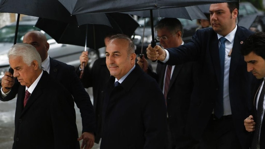 """Turkish Foreign Minister Mevlut Cavusoglu, center, and Turkish Cypriot leader Dervis Eroglou, left, leave their meeting, following a press conference in the Turkish Cypriot breakaway north of the divided capital Nicosia, Wednesday, Jan. 14, 2015. United Nations envoy for Cyprus, Norway's Espen Barth Eide says deadlocked talks to reunify ethnically split Cyprus are """"moving in the wrong direction"""" amid a dispute over rights to search for offshore gas. Cavusoglu is in Cyprus for one-day visit for talks. (AP Photo/Petros Karadjias)"""