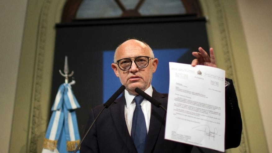 Argentina's Foreign Minister Hector Timmerman shows a letter that he said was sent in 2013 to Interpol's Secretary General Ronald Noble informing him of the agreement reached with Iran's government to investigate the 1994 bombing of the Argentine-Israeli Mutual Association  that killed 85 people,  in Buenos Aires, Argentina, Thursday, Jan. 15, 2015.  Argentine prosecutor Alberto Nisman accused President Cristina Fernandez of reaching a secret deal with Iran to avoid punishing those responsible. (AP Photo/Rodrigo Abd)