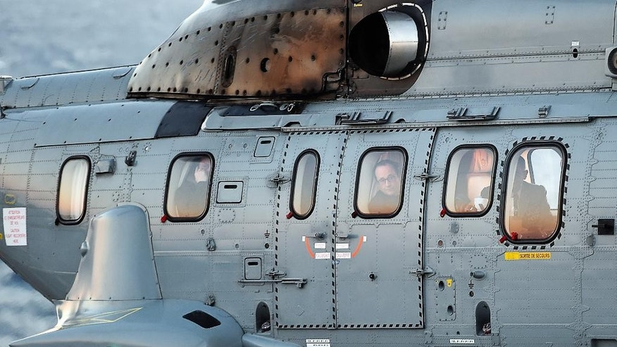 French President Francois Hollande is seen through the window of a helicopter as he leaves after giving a New Year's speech to military troops aboard the French nuclear aircraft carrier Charles de Gaulle, off the coast of Toulon, southern France, Wednesday, Jan. 14, 2015. France ordered prosecutors around the country to crack down on hate speech, anti-Semitism and those glorifying terrorism and announced Wednesday it was sending an aircraft carrier to the Mideast to work more closely with the U.S.-led coalition fighting Islamic State militants. (AP Photo/ Anne Christine Poujoulat, Pool)