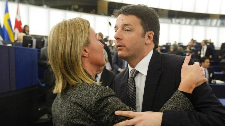 Italian Prime Minister Matteo Renzi, right, kisses high representative for EU foreign affairs Federica Mogherini at the European Parliament in Strasbourg, eastern France, Tuesday Jan. 13, 2015.  Renzi delivered a statement as president in office of the European Union. (AP Photo/Christian Lutz)