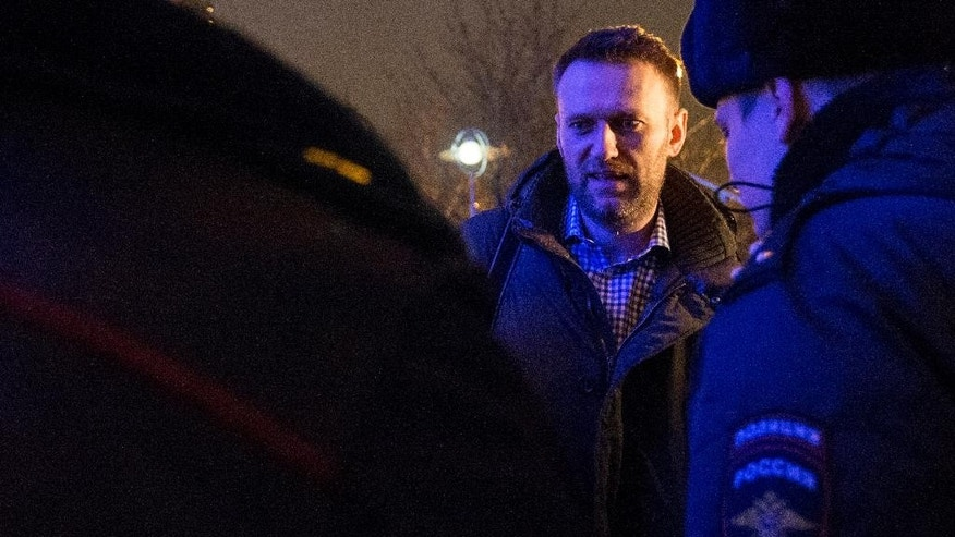Russian opposition activist and anti-corruption crusader Alexei Navalny, background is detained by police officers after defying his house arrest to speak on Radio Echo Moskvy in Moscow, Wednesday, Jan. 14, 2015. Leading Russian opposition figure Alexei Navalny says he has paid the state for the electronic bracelet that he cut off to protest his house arrest. Navalny was convicted in late December of fraud and given a suspended sentence. But the court said he must remain under house arrest until his appeals are exhausted. (AP Photo/Pavel Golovkin)