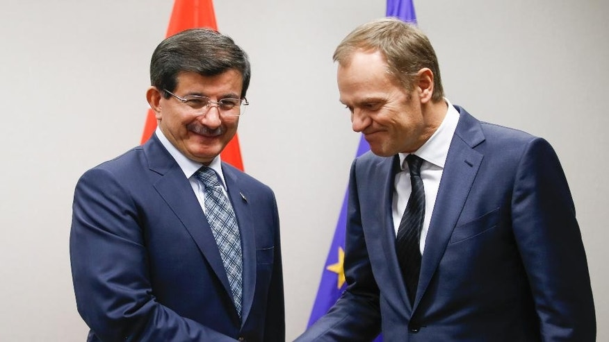 European Council President Donald Tusk, right, welcomes Turkey's Prime Minister Ahmet Davutoglu at his office at the EU Council in Brussels on Thursday, Jan. 15, 2015. (AP Photo/Olivier Hoslet, Pool)