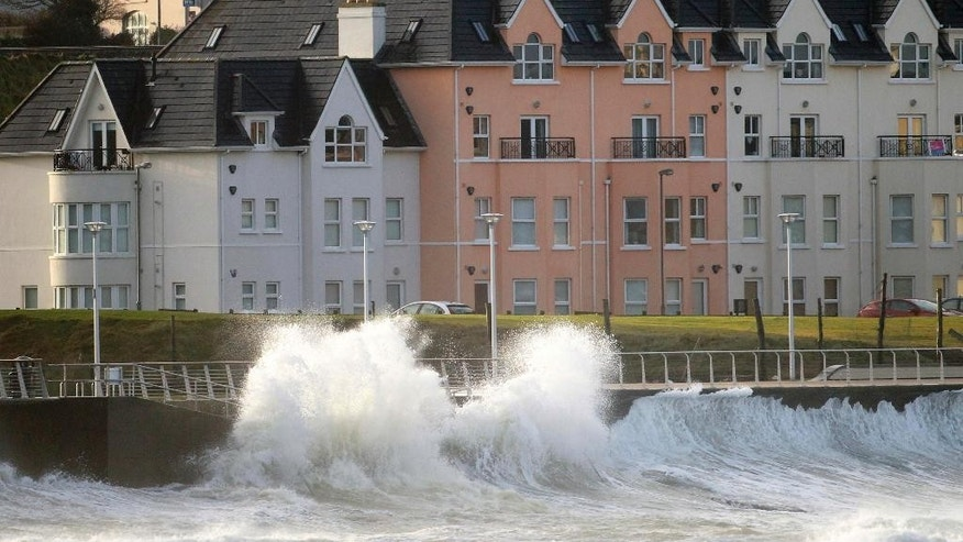 Waves crash against the sea defences in Portrush, Northern Ireland, Thursday, Jan. 15, 2015.  Thousands of homes across Ireland have been left without power after storm force winds battered the country overnight leaving thousands of homes without power. A storm swept in from the Atlantic late Wednesday night, bringing torrential rain and winds of up to 150km/h.  (AP Photo/Peter Morrison)