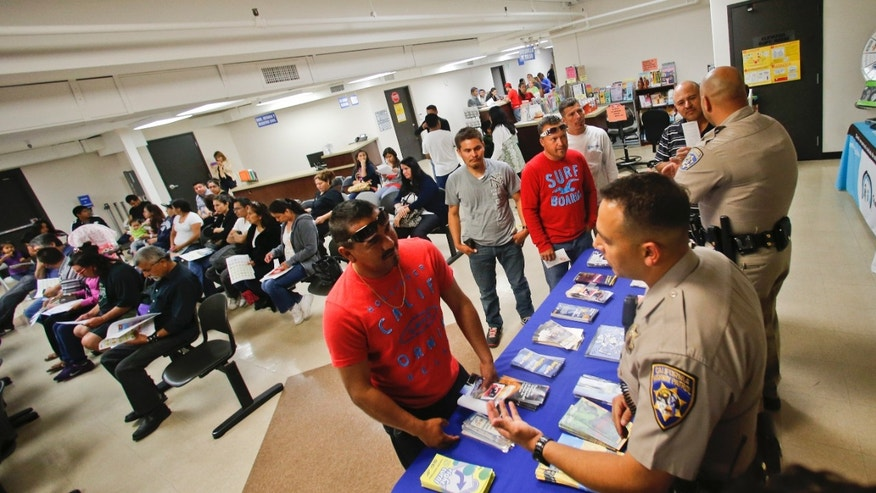 California Highway Patrol officers Armando Garcia, right, and Ray Patton explain to immigrants the process of getting a drivers license during an information session at the Mexican Consulate, in San Diego.