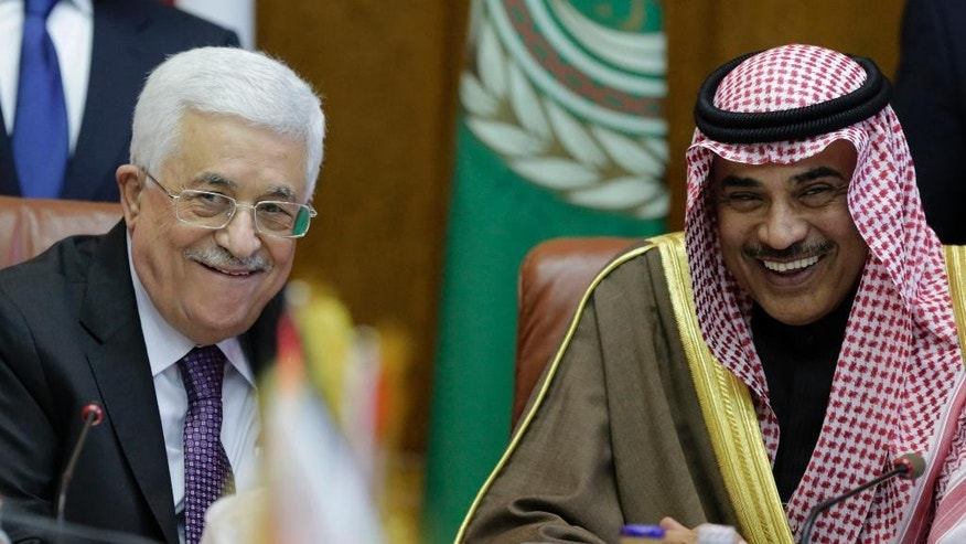 Palestinian President Mahmoud Abbas, left, and Kuwaiti Foreign Minister Sabah al-Khaled al-Sabah smile during an Arab foreign ministers urgent meeting at the Arab League headquarters in Cairo, Egypt, Thursday, Jan. 15, 2015. (AP Photo/Amr Nabil)