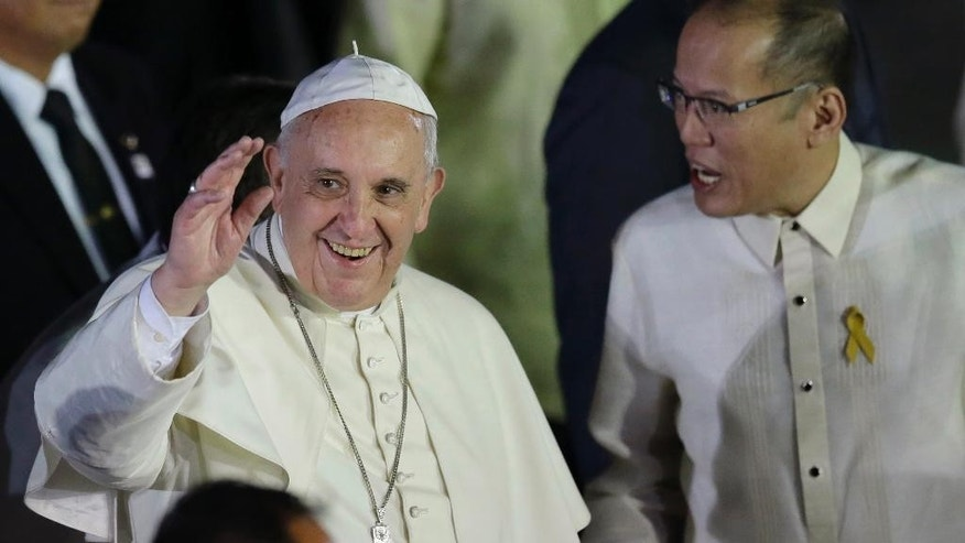 Pope Francis waves to well-wishers upon arrival from Sri Lanka Thursday, Jan. 15, 2015 at suburban Pasay city, south of Manila, Philippines. Pope Francis arrived for the first papal visit to the Philippines in 20 years. At right is Philippine President Benigno Aquino III who broke protocol to welcome the Pontiff. (AP Photo/Bullit Marquez)