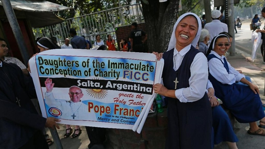 Filipina Sister Alodia Abarca, 40, of the Daughters of the Immaculate Conception of Argentina, unfurls a poster that she hopes will draw the attention of Pope Francis, also from Argentina, as he passes along the motorcade route in Manila, Philippines, Thursday, Jan. 15, 2015. Pope Francis arrives Thursday from Sri Lanka for a pastoral visit which is expected to draw millions of faithful where about 81-percent of the population is Catholic. (AP Photo/Wally Santana)