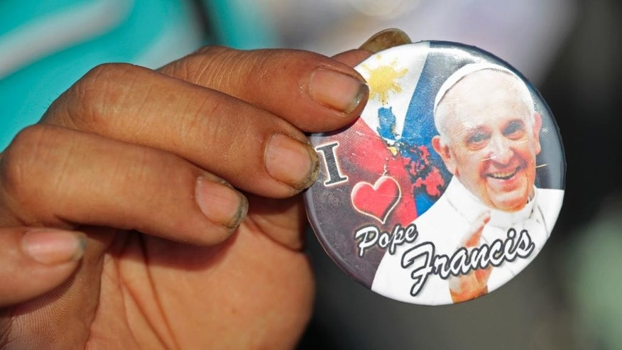 A street vendor displays a Pope Francis souvenir along the motorway in Manila, Philippines, Thursday, Jan. 15, 2015. Pope Francis arrives Thursday from Sri Lanka for a pastoral visit which is expected to draw millions of faithful where about 81-percent of the population is Catholic. (AP Photo/Wally Santana)