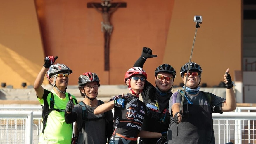 "Bicyclists pose for a ""selfie"" in front of a crucifix where Pope Francis will deliver a mass during his visit in Manila, Philippines, Thursday, Jan. 15, 2015. Pope Francis arrives Thursday from Sri Lanka for a pastoral visit which is expected to draw millions of faithful where about 81-percent of the population is Catholic. (AP Photo/Wally Santana)"