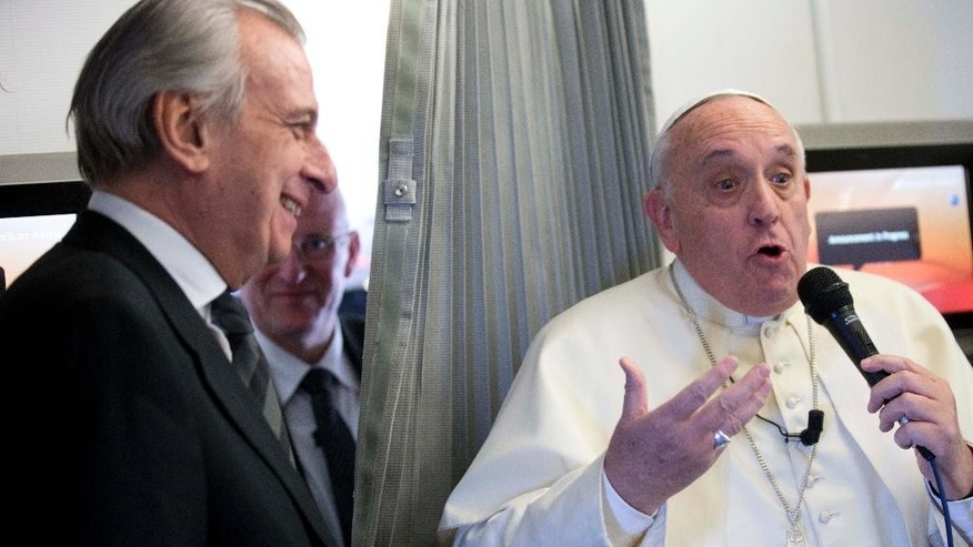 Pope Francis jokes with Alberto Gasbarri, Pope's trip organizer, as he meets reporters during his flight from Sri Lanka to the Philippines, Thursday, Jan. 15, 2015. (AP Photo/Alessandra Tarantino, Pool)