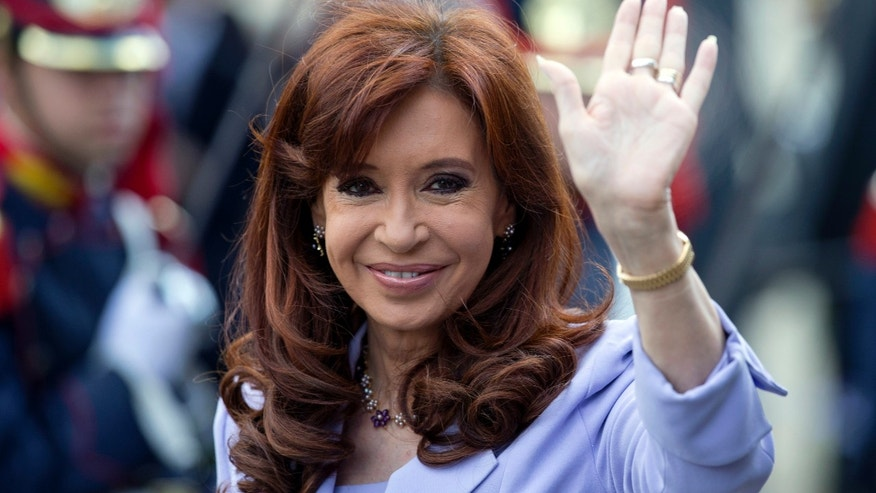 In this Dec. 17, 2014 photo, Argentina's President Cristina Fernandez waves to journalists during the Mercosur Summit in Parana, Argentina. Less than a year before presidential elections set for Oct. 2015, it's uncertain who'll succeed Fernandez. (AP Photo/Natacha Pisarenko)