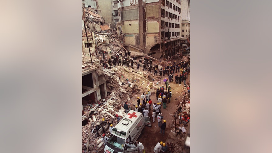 FILE - In this July 18, 1994 file photo, firefighters and rescue workers search through the rubble of the Argentine-Israeli Mutual Association community center, after a car bomb rocked the building in downtown Buenos Aires, Argentina. In a statement released Wednesday, Jan. 14, 2015, Argentine Prosecutor Alberto Nisman, who is investigating the 1994 bombing of the Jewish community center, accused President Cristina Fernandez of reaching a deal with Iran to avoid punishing those responsible. (AP Photo/Alejandro Pagni, File)