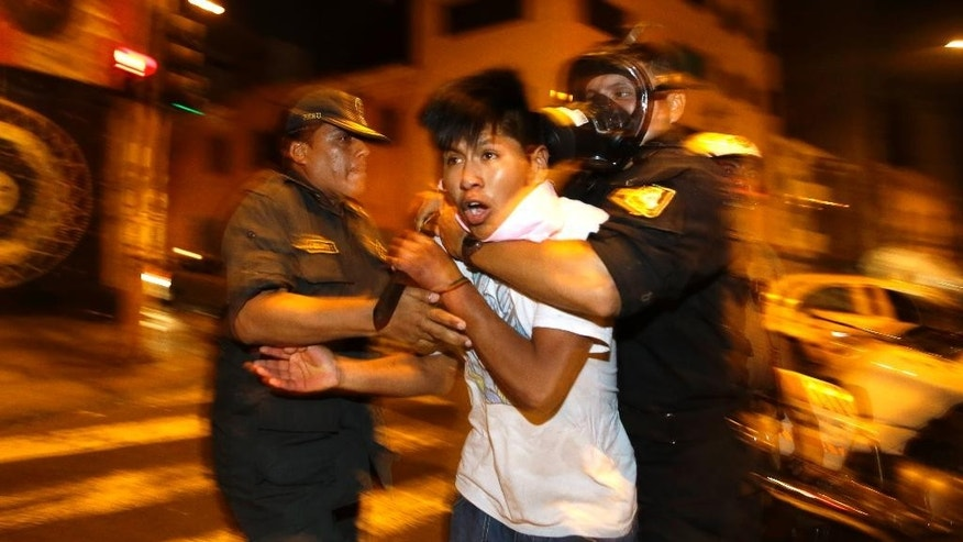 Police detain a young man who identified himself as a working student as he protests a new labor law that affects young workers in Lima, Peru, Thursday, Jan. 15, 2015. This is the fourth protest by youths in the last month since Peru's Congress approved in December a controversial law that eliminates some labor rights for workers age 18 to 24. The law takes away their right to severance pay, two annual bonuses, and reduces vacation time from 30 to 15 days per year. (AP Photo/Martin Mejia)