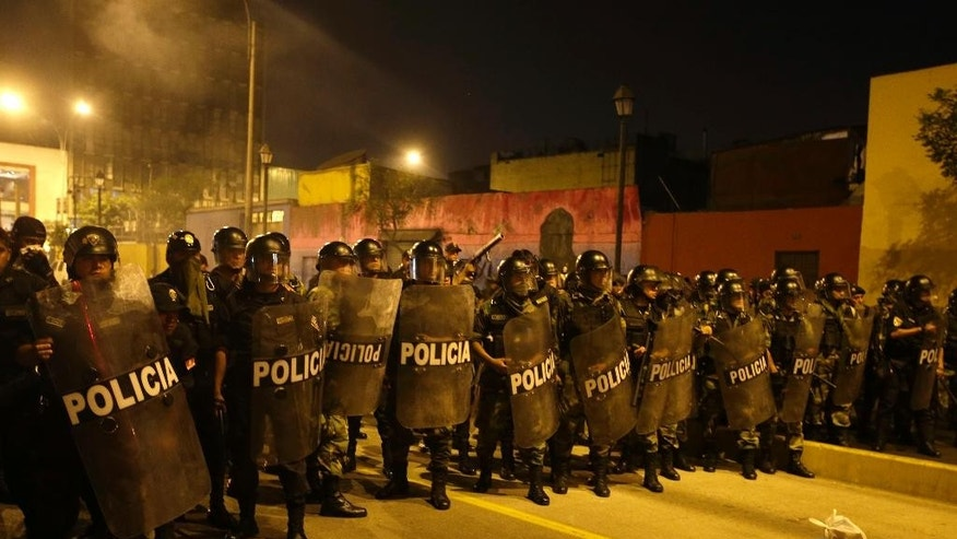 Police confront students to disperse their protest against a new labor law that affects young workers in Lima, Peru, Thursday, Jan. 15, 2015. It was the fourth protest by youths in the last month since Peru's Congress approved in December a controversial law that eliminates some labor rights for workers age 18 to 24. The law takes away their right to severance pay, two annual bonuses, and reduces vacation time from 30 to 15 days per year. (AP Photo/Martin Mejia)