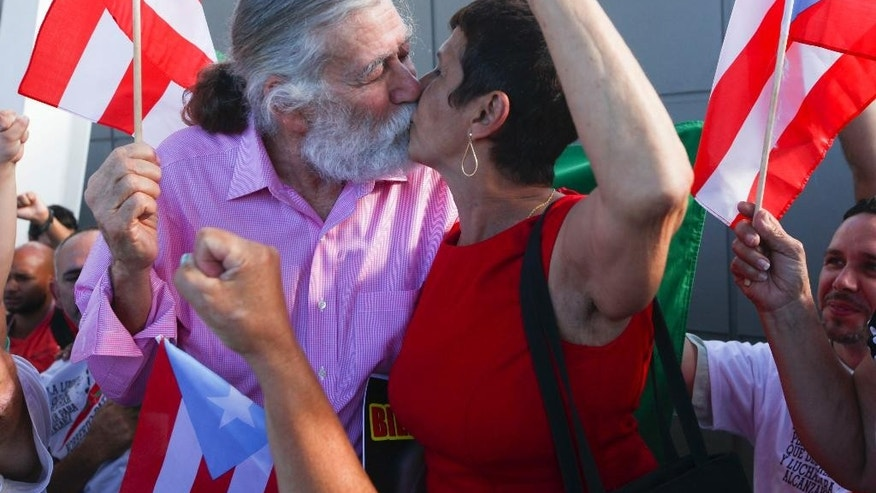 Norberto Gonzalez Claudio, left, who completed a prison sentence for his role in a 1983 holdup in Connecticut carried out by Puerto Rican militants, kisses his wife Elda Santiago as he's greeted by supporters raising their fists and waving their nation's flag at the international airport in Carolina, Puerto Rico, Thursday, Jan. 15, 2015. The 69-year-old Puerto Rican arrived Thursday in the U.S. territory just hours after he was released from a prison in central Florida. (AP Photo/Gerardo Bello)