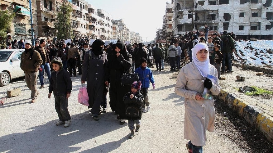 Hundreds of Syrians walk on a street with damaged buildings before going out of town to buy food and other essential materials as they go through a military checkpoint in the town of Beit Sahm, south of the capital, Damascus, Syria, Wednesday, Jan. 14, 2015. (AP Photo)