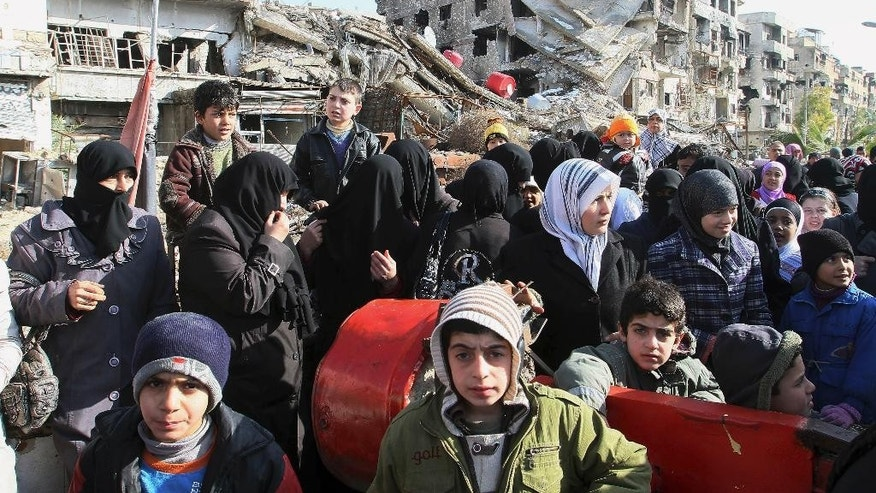 Hundreds of Syrians mingle amid rubble before going out of town to buy food and other essential materials as they wait in line at a military checkpoint in the town of Beit Sahm, south of the capital, Damascus, Syria, Wednesday, Jan. 14, 2015. (AP Photo)