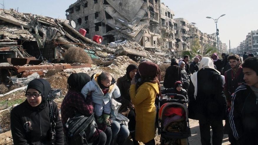 Hundreds of Syrians sit amid rubble before going out of town to buy food and other essential materials as they wait at a military checkpoint in the town of Beit Sahm, south of the capital, Damascus, Syria, Wednesday, Jan. 14, 2015. (AP Photo)
