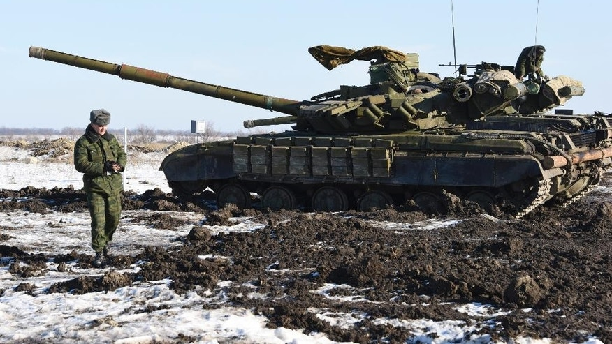 In this Wednesday, Jan. 14, 2015 photo Russian-backed separatist walks past tanks at the check-point north of Luhansk, Eastern Ukraine.  An attack on a passenger bus in eastern Ukraine killed 12 people Tuesday, likely dealing the final blow to hopes that a short-lived and shaky cease-fire could take hold. (AP Photo/ Mstyslav Chernov)