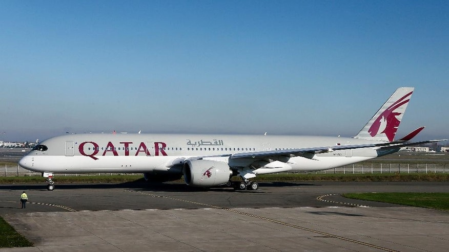 FILE - In this Monday. Dec. 22, 2014 file photo, the first Airbus A350 for Qatar Airways sits on the tarmac during the hand over ceremony in Toulouse, southwestern France. The world's newest jetliner, the Airbus A350, took to the skies Thursday, Jan. 15, 2015 carrying its first paying passengers from the Gulf Arab nation of Qatar.(AP Photo/Fred Lancelot, File)