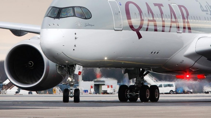 The new Airbus A 350 of Qatar Airways coming from Doha, Qatar, approaches the gate at the airport in Frankfurt, Germany, Thursday, Jan. 15, 2015. Qatar Airways is the first airline in the world to fly the Airbus A 350. (AP Photo/Michael Probst)