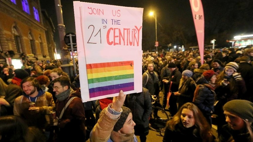 "Protestors hold a poster which reads "" Join us in the 21st century"" during an protest in support of gay kissing, in Vienna, Austria, on Friday, Jan. 16, 2015.  The protest was called after the manager of a cafe in Vienna told a smooching lesbian couple to leave. (AP Photo/Ronald Zak)"