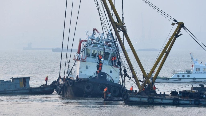 "In this photo released by China's Xinhua News Agency, rescuers approach the lifted wreckage of capsized tug boat ""Wanshenzhou 67"" on the Yangtze River near Jingjiang, east China's Jiangsu Province,  Saturday, Jan. 17, 2015. Authorities confirmed 21 people dead in the capsizing of the tugboat with an international team on a test voyage in eastern China, after rescuers dragged the overturned vessel to shallow waters and scoured it Saturday. (AP Photo/Xinhua, Shen Peng) NO SALES"